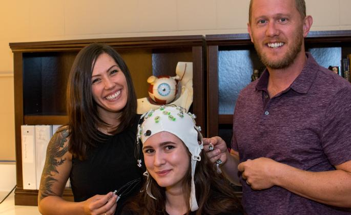 Student Olivia Krieger, left, and Professor Jesse Bengson demonstrate a cap used to record brainwaves with student Alexandra Theodoroub