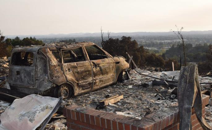 A destroyed car looks out over Santa Rosa to the west on Alturia Drive near the boulders at Fountaingrove, where hundreds of homes were lost in the Oct. 9 firestorm. // Photo by Paul Gullixson