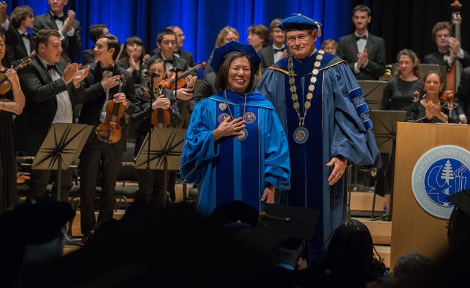 judy sakaki in ceremony with chancellor timothy white