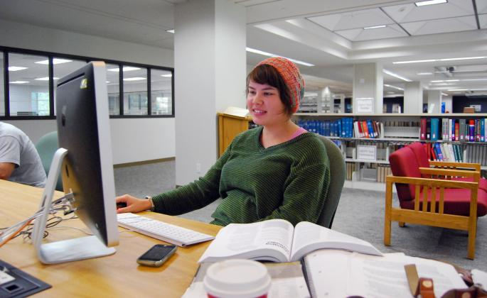 Student using computer and books in library