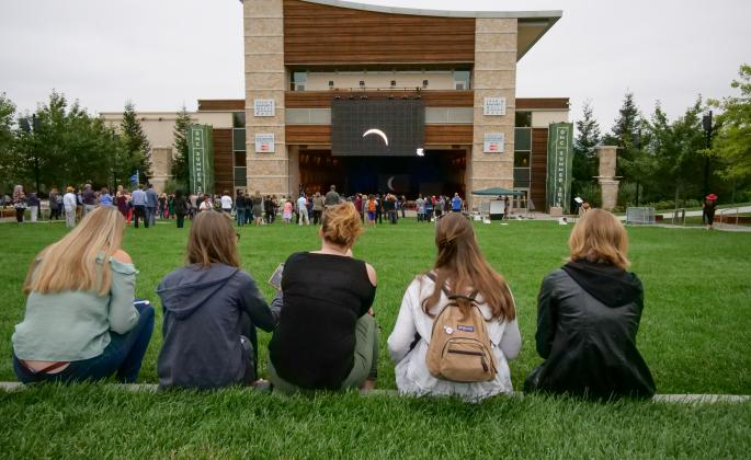 Students watch the eclipse on the big screen outside Weill Hall