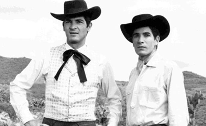 "Still from Arturo Ripstein's film ""Tiempo De Morir"" (1966). Two men in vaquero attire"