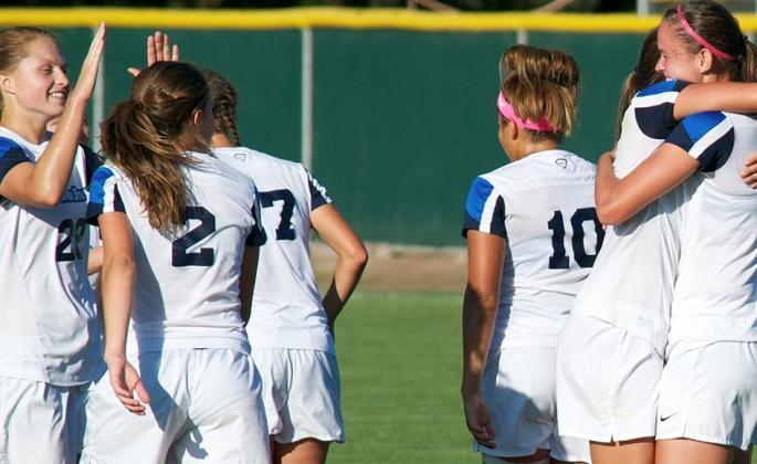 women's soccer celebrating goal