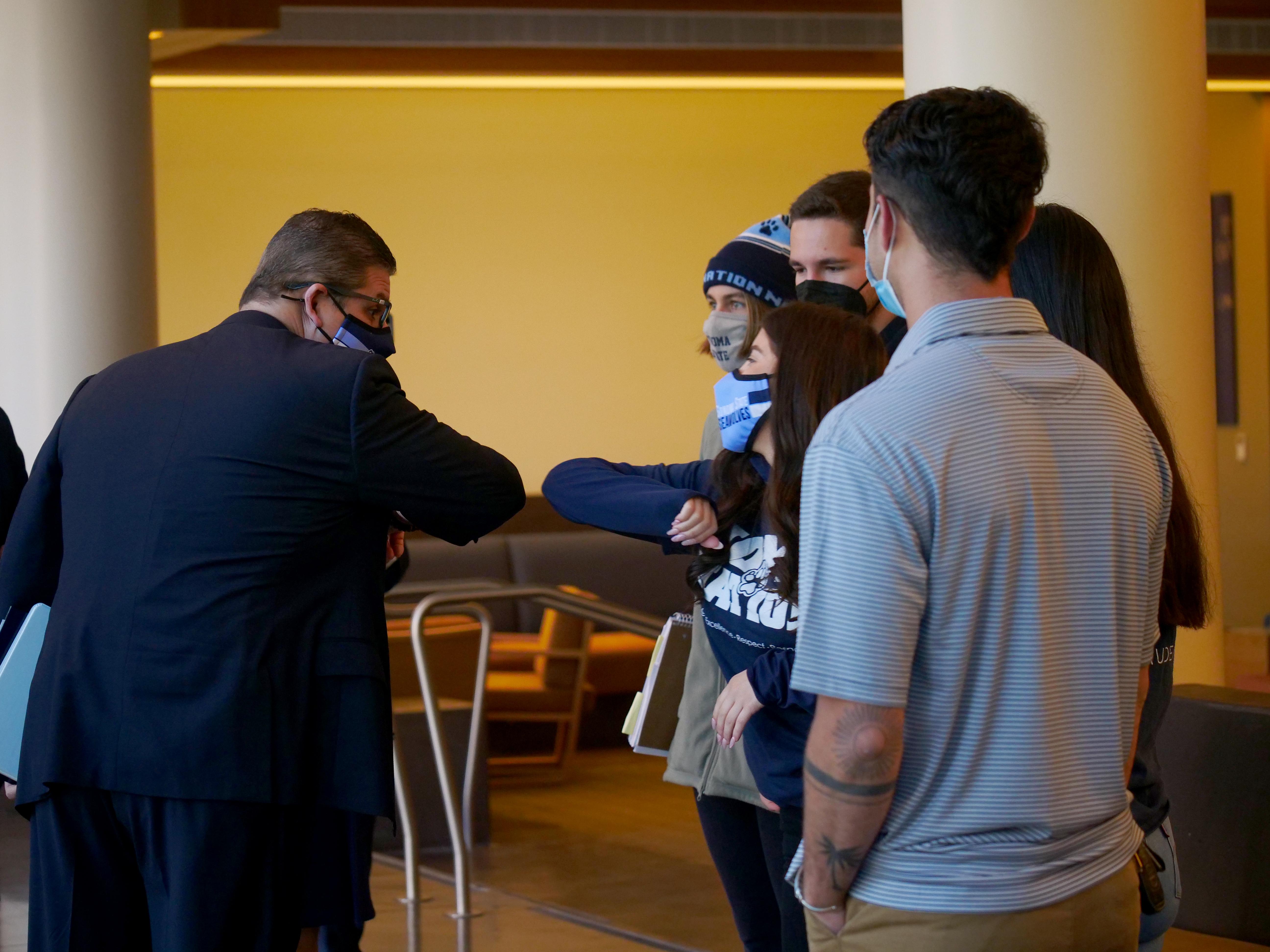 Chancellor Castro elbow bumps an SSU student