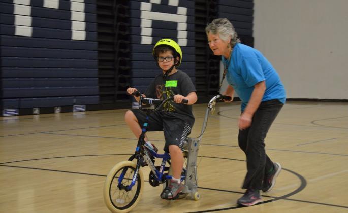 elaine mchugh helping a child ride a bike