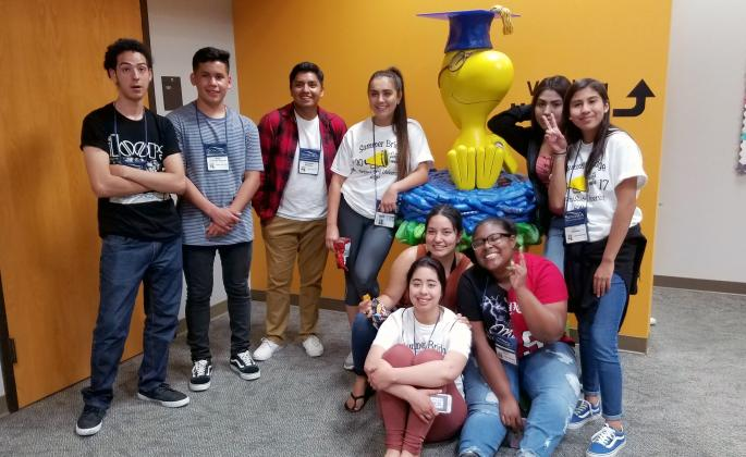 students pose with Woodstock sculpture in library