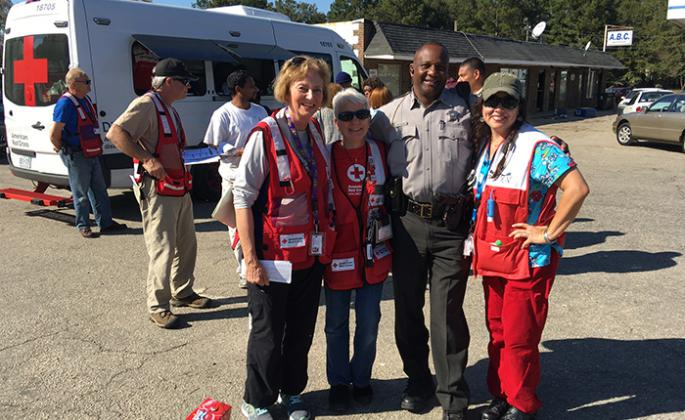Ann Gang, Sally Bowers, a local police officer and Kathy De Bel help residents recover from Hurricane Matthew in North Carolina.