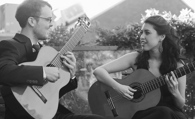 man and woman with acoustic guitars