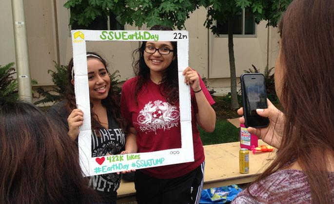 students pose for photo at earth day event on campus