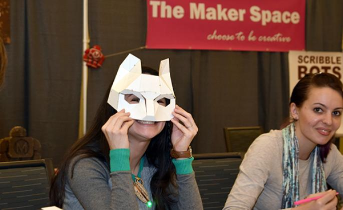 woman holding up paper fox mask